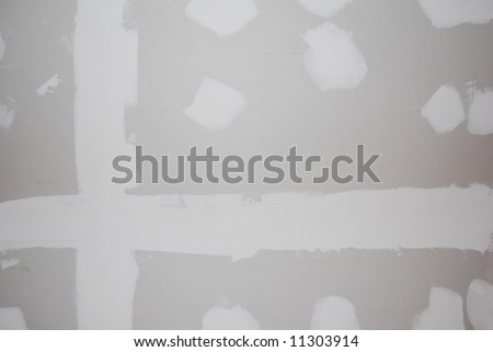 A sheetrock or drywall background.  The taping and spackling have been done in this shot. - stock photo