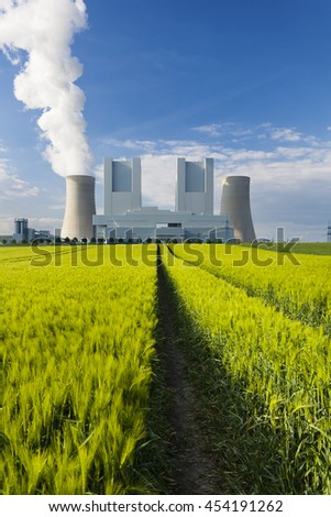 A shiny new lignite power station behind a rye field with wheel tracks leading to it