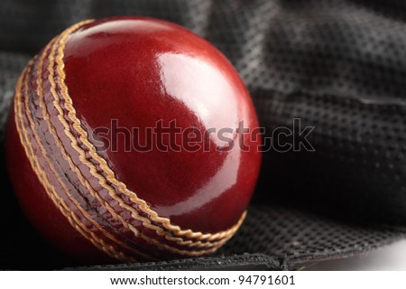 A shiny, new test match cricket ball in a wicket keeping glove. - stock photo