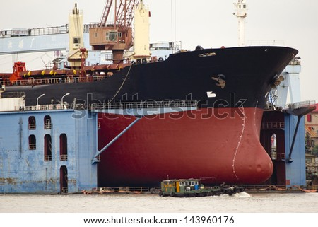 A ship in a dry dock for repairs, Shanghai, China - stock photo