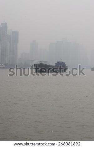 a ship in huangpu river, haze, fog, bad air condition - stock photo