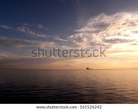A ship in the distant horizon sailing on the ocean. - stock photo