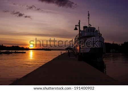 A ship is docked at a wharf during sunset on a lake.  - stock photo
