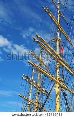 A ship mast against a blue sky - stock photo