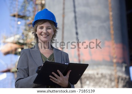 A shipping engineer in front of an oil platform in the harbor - stock photo