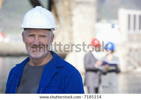 A shipping engineer in front of an oil platform in the harbor, with coworkers behind him - stock photo