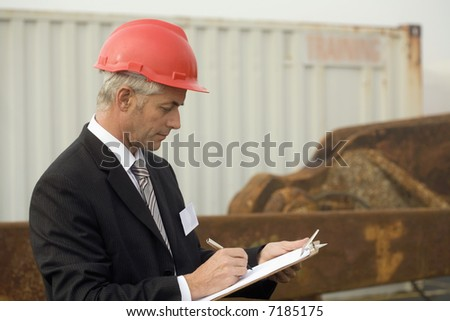 A shipping engineer taking notes in the early morning fog, with a large rusted anchor behind him - stock photo