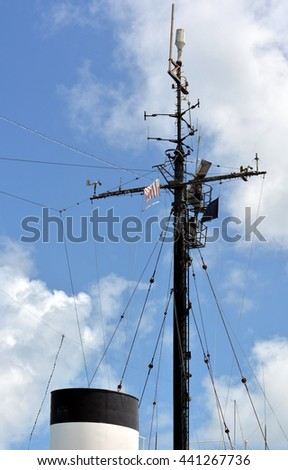 A ships smoke stack and mast against blue sky with clouds. - stock photo