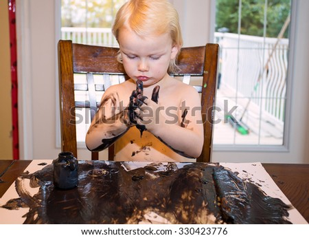 A shirtless little girl sitting at a table playing with black paint and paper