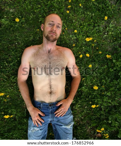 a shirtless man surrounded by weeds - stock photo