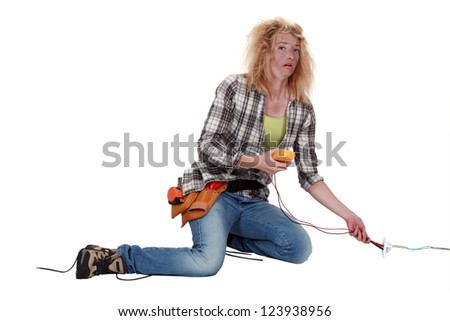 A shocked female electrician. - stock photo