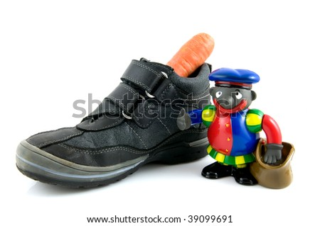 A shoe with carrot and black piet a Dutch tradition Sinterklaas isolated on white background - stock photo