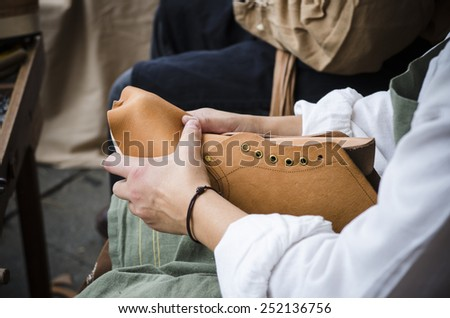 A shoemaker manufactures boots - stock photo