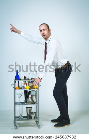 A shoot of young caucasian men as a barmen doing a cocktail. - stock photo