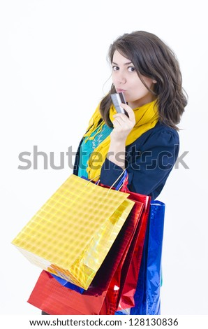 A shopaholic girl holding a credit card coming from shopping - stock photo