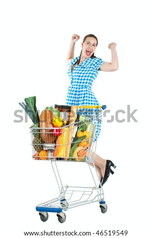 A shopper with a full cart of fresh groceries jumping for joy