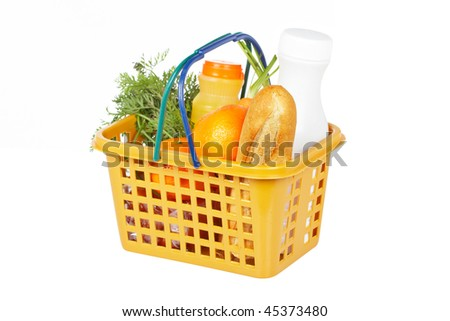 A shopping basket full of groceries isolated on white background. Shallow depth of field - stock photo