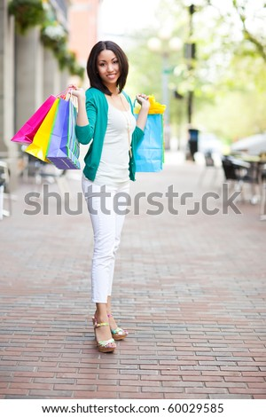 A shopping black woman carrying shopping bags outdoor - stock photo