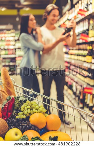 A shopping cart full of food, in the background beautiful young couple is choosing a beverage in the supermarket