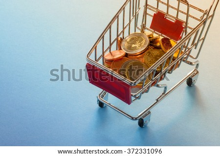 A shopping cart with euro coins, symbolic photo for purchasing power and consumption - stock photo