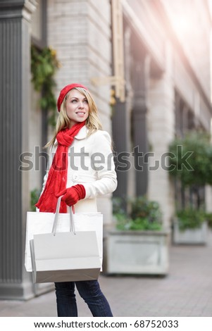 A shopping caucasian woman carrying shopping bags at an outdoor shopping mall