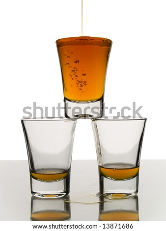 A shot being poured over two almost empty shots. - stock photo