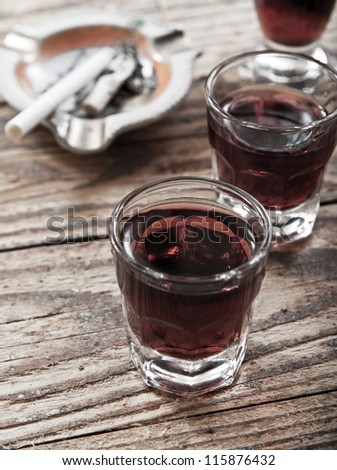 A shot glass full of alcohol and  cigarette butts  on table - stock photo
