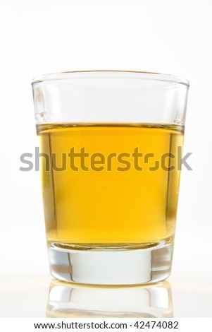 A shot glass of amber colored alcohol against a white vackground