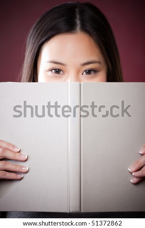 A shot of a beautiful asian college student reading