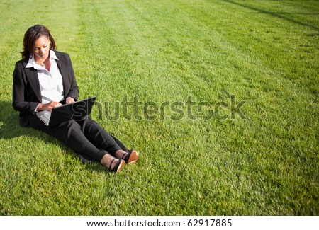 A shot of a beautiful black businesswoman working on her laptop outdoor - stock photo