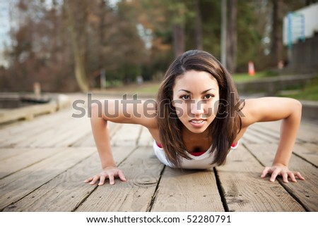 A shot of a beautiful black woman doing push up outdoor