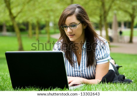 A shot of a beautiful caucasian businesswoman typing on her laptop outdoor