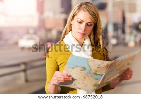 A shot of a beautiful caucasian traveling woman reading a map