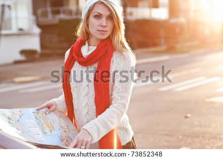 A shot of a beautiful caucasian traveling woman reading a map - stock photo