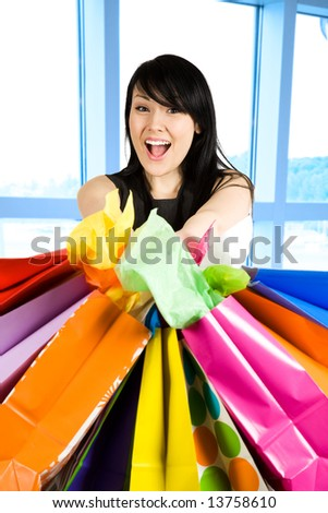 A shot of a beautiful woman carrying shopping bags in a store - stock photo
