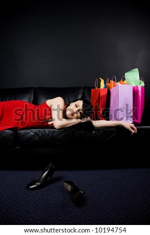A shot of a beautiful woman resting on a sofa after a shopping trip