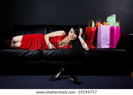 A shot of a beautiful woman resting on the sofa after shopping - stock photo