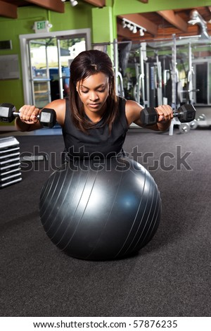 A shot of a black female athlete training and lifting weights - stock photo