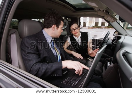 A shot of a businessman and businesswoman sitting in a car looking at a laptop. - stock photo