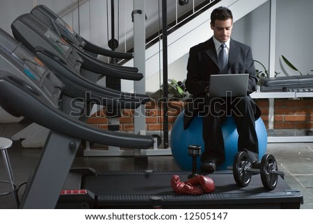 A shot of a businessman, in suit, checking email by row of treadmills. - stock photo