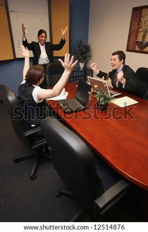 A shot of a businesswoman presenting to a businessman and businesswoman.  All three have their hands up in excitement. - stock photo
