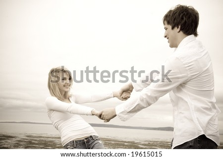 A shot of a caucasian couple having fun on the beach in sepia - stock photo