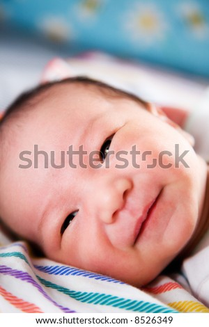 A shot of a cute asian baby boy smiling - stock photo