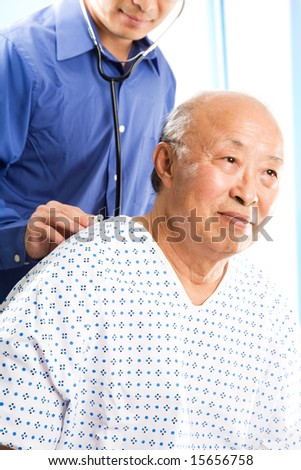 A shot of a doctor examining a senior asian patient in a hospital - stock photo