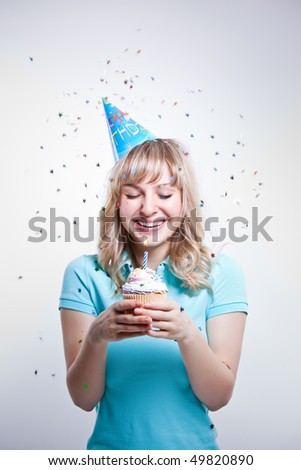 A shot of a girl celebrating her birthday holding a cupcake - stock photo