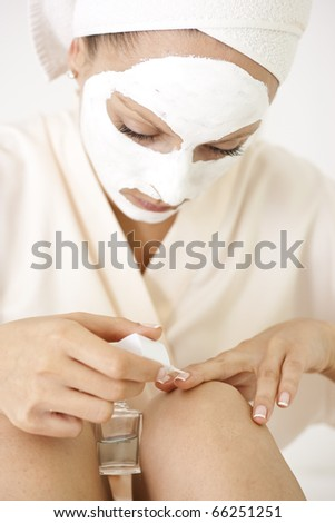 A shot of a girl in beautification process applying nail polish