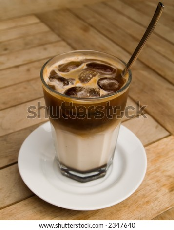 A shot of a glass of ice cold coffee on a wooden table. Front of the glass in focus.