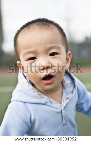 A shot of a happy asian boy having fun outdoor - stock photo