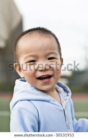 A shot of a happy asian boy laughing