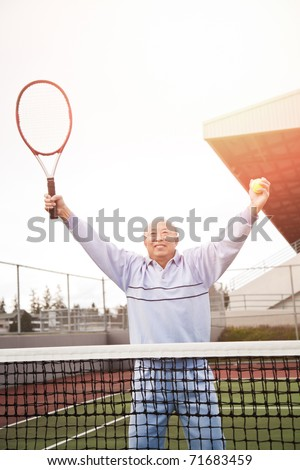 A shot of a happy asian senior tennis player playing tennis - stock photo